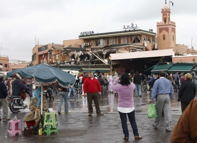 Tourists have their picture taken in the Marrakesh square where the bomb hit