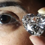 In this April 1, 2011 file photo a Christie's employee presents an unmounted heart-shaped diamond, D colour, internally flawless, type IIa diamond, weighing 56.15 carats, with excellent polish and symmetry during a press preview in Geneva, Switzerland. (AP Photo/Keystone, Christian Brun, File)