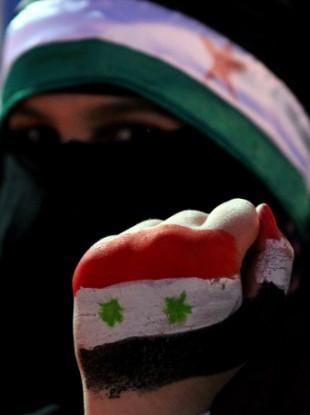 A Syrian protester at a demonstration in Jordan demanding Assad's resignation.