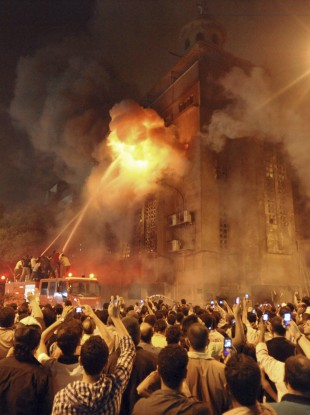Firemen fight a fire at a church surrounded by angry Muslims in the Imbaba neighborhood in Cairo