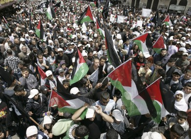Demonstrators wave Palestinian flags during a rally in the West Bank city of Ramallah on Sunday.