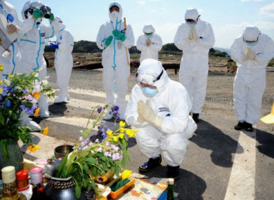 15 May 2011: The governor of Fukushima and others wearing radiation protection suits offer prayers for the victims of the 11 March disasters.