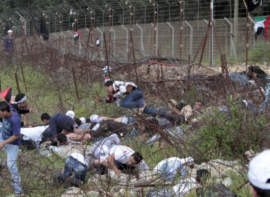 Palestinian protesters take cover after Israeli soldiers opened fire at them during their rally.