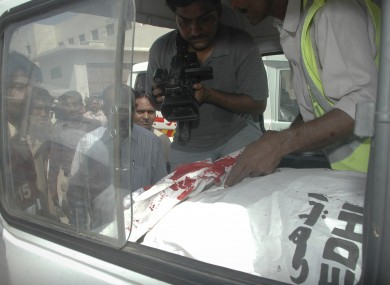 A Pakistani cameraman records video of a Saudi consulate employee who was shot dead in Karachi, Pakistan on Monday.