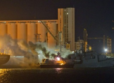 Smoke rises from a ship struck during an airstrike at Tripoli port early today.