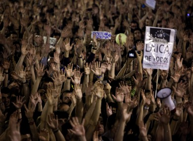 Demonstrators rise their hands as they shout slogans during a protest at Sol square, in Madrid on Friday.