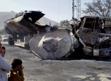 Local children survey the damage to the burnt out oil tanker.