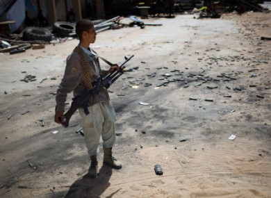 A rebel fighter stands amid fired munitions at the front line between the rebels and Gaddafi's forces 25km west of Misrata today.