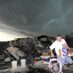 Mark Siler carries some salvageable items from the house of his friend Clay Warden as another storm approaches Joplin today. Warden's house was destroyed yesterday by a tornado. (AP Photo/Mike Gullett)