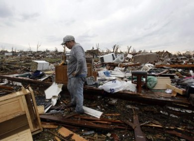 Josh Ramsey looks through the rubble of his mother-in-law's home following yesterday's tornado in Joplin, Missouri.
