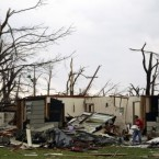 A man carries a box out of a house damaged by the tornado in Joplin. (AP Photo/Jeff Roberson)