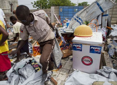 A municipal worker carries away a tent used by a family during an eviction at an earthquake displaced camp in Port-au-Prince, Haiti.