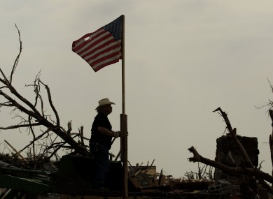 One man raises the American flag as he helps clean up the devastation.