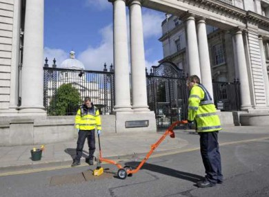 Gardai seal manhole covers outside Government Buildings this morning ahead of the visit of Queen Elizabeth next week