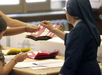 A nun prepares to cast her ballot at a polling station in Rome yesterday in the first of two days of voting.