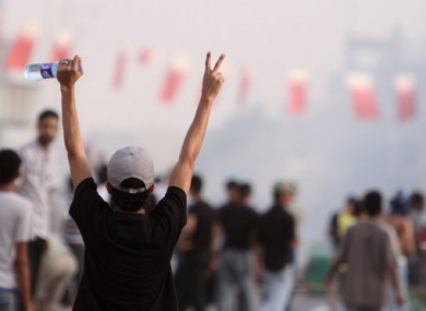 Anyi-government protesters gesture at riot police on 23 March 2011 in Malkiya, Bahrain.