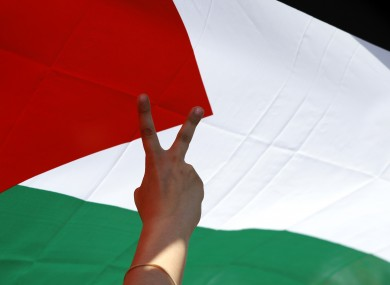 A 'V' for victory sign in front of a Palestinian flag (File photo)