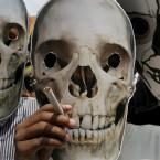 Indian street children wear human skull masks during a