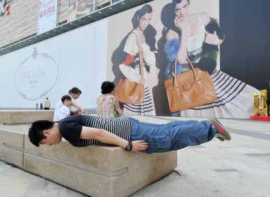 A man planks on a street in Shenyang, China. A New Zealand school has been criticised for organising a planking competition for its students.