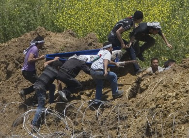 Protesters attempt to rescue a man shot by Israeli troops along the Syrian border on Sunday.