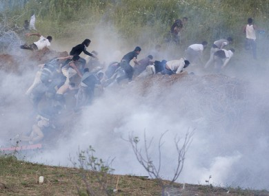 Protesters retreat from the border after Israeli forces fired tear gas yesterday.