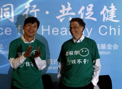 Baidu CEO, Robin Li, left, and Microsoft founder Bill Gates, right, smile wearing green t-shirts with the words