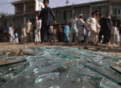 Afghans walk past the debris at the site of an explosion in Laghman province today.