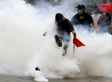 A demonstrator kicks away a tear gas canister outside the Parliament in central Athens, during a rally against plans for new austerity measures