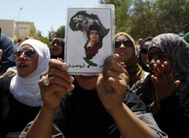 Libyan students chant pro-Gaddafi slogans outside a damaged university building in Tripoli, Libya, today.