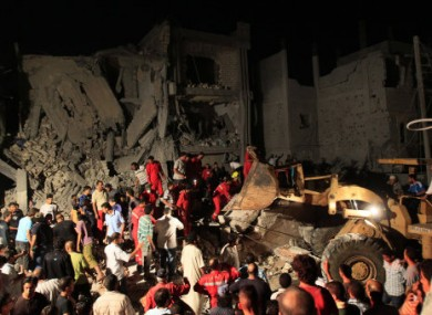 Photo taken on government-organised tour showing Libyan firefighters and local residents removing debris from damaged buildings in Tripoli today.