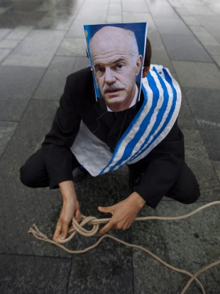 A protester with a mask of prime minister George Papandreou prepares himself as a marionettes prior to a protest in Athens.