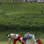 McIlroy and YE Yang, of South Korea, mark their balls on the 10th green during the final round.