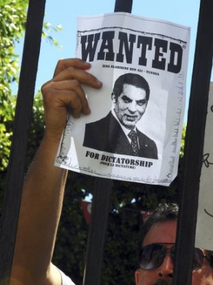 A demonstrator holds a poster showing Ben Ali outside the Tunis Criminal Court which is hearing two embezzlement, money laundering and drug trafficking cases against Zine El Abidine Ben Ali