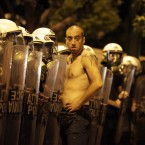A topless protester stands in front of Greek riot police officers following a rally against plans for new austerity measures (AP Photo/Lefteris Pitarakis)