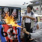 A North Korean defector burns pictures of Kim Jong Il and his son Kim Jong Un during a rally in Seoul, South Korea (AP Photo/Lee Jin-man)