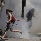 Protesters run to avoid tear gas thrown by riot police during a demonstration in Athens. Pic: AP Photo/Petros Giannakouris