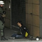 A riot police officer guards an arrested protester during a demonstration in Athens. Pic: AP Photo/Petros Karadjias