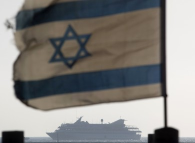 An Israeli flag and in the distance the Mavi Marmara which was stormed by Israeli soldiers in a bloody confrontation last year. (File photo)