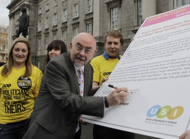 Ruairí Quinn signs a USI pre-election pledge not to cut student grants, or raise fees, in government.