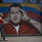 A woman walks by a gate with a painting depicting Venezuela's President Hugo Chavez, who today admitted he is suffering from cancer (AP Photo/Ariana Cubillos)