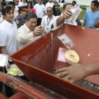 Filipinos throw pirated DVD's into a mechanised grinder during a ceremonial destruction of counterfeit goods seized in raids (AP Photo/Bullit Marquez)