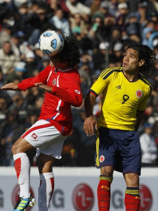 Costa Rica's Randall Brenes, left, heads the ball as Colombia's Radamel Falcao looks on.