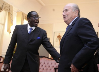 FIFA President Sepp Blatter, right, is greeted by Zimbabwean President Robert Mugabe, during his visit to Zimbabwe on Monday.