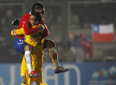 Chile's Gonzalo Jara celebrates with goalkeeper Claudio Bravo.