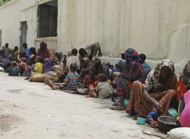 Somalis wait outside a building as they wait to go to an internally displaced camp in Mogadishu.