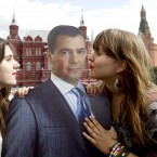 Two women kiss a lipstick-smeared cutout of Russian President Dmitry Medvedev in Red Square, Moscow, to mark International Kissing Day (AP Photo/Ivan Sekretarev)