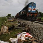 A train passes by the wreckage after another train hit a bus at Kanshiramnagar, India. At least 35 people died (AP Photo/Pankaj Nangia)