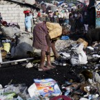 An elderly woman searches the trash for useful items in Port-au-Prince, Haiti (AP Photo/Dieu Nalio Chery)