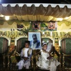 Children sit in front of a picture of Libyan leader Muammar Gaddafi before a group wedding party for 25 couples in Tripoli (AP Photo/Tara Todras-Whitehill)