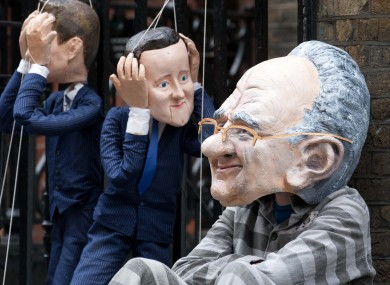 Puppets of Nick Clegg, David Cameron and Rupert Murdoch outside Murdoch's home in London this morning.
